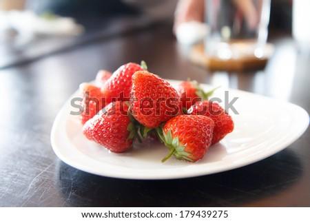 fresh strawberries on white plate - stock photo