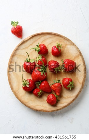 fresh strawberries on wooden plate, food top view - stock photo