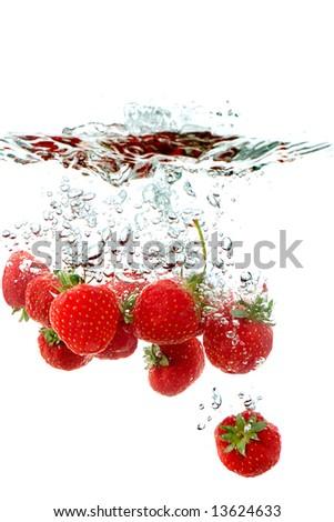 fresh strawberries splashing into water - stock photo
