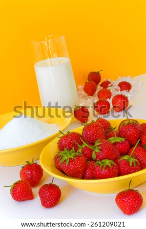 Fresh strawberries, sugar and a glass of milk arranged on white ground against yellow background, ingredients for delicious strawberry milkshake - stock photo