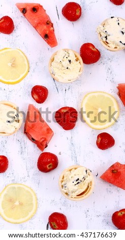Fresh strawberries, watermelon, lemon and delicious ice cream in a crispy wafers on a white wooden table. Seasonal summer background. - stock photo