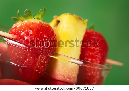 Fresh strawberry and pineapple garnish on skewers on the rim of a glass (Selective Focus, Focus on the front of the strawberry)