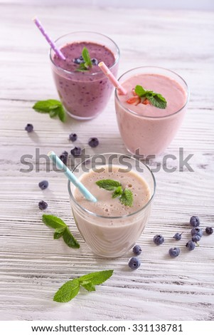 Fresh strawberry, blueberry and milk yogurts with mint and berries around on light wooden background