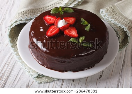 Fresh strawberry cake with chocolate topping on a table close-up. Horizontal