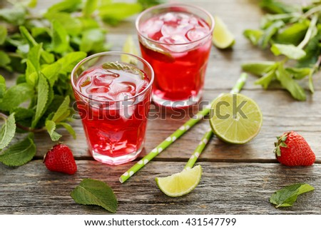 Fresh strawberry drink in glass with lime on wooden table - stock photo