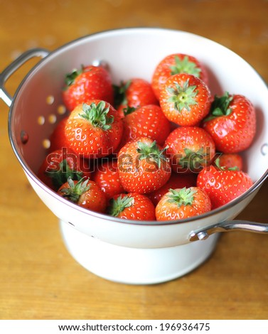 Fresh strawberry harvest in a white colander on a kitchen wooden table - stock photo