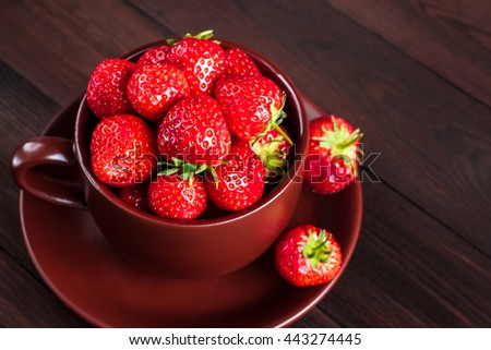 Fresh strawberry in a cup on wooden background. Creative strawberry close-up - stock photo