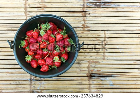 Fresh strawberry in bucket on bamboo wood panel - stock photo