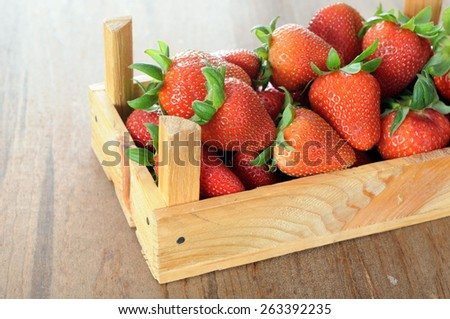 fresh strawberry in wooden crate on table  - stock photo