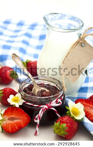Fresh strawberry jam in a jar of strawberries with milk on a wooden background - stock photo