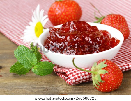 fresh strawberry jam in a white bowl on the table, rustic style - stock photo