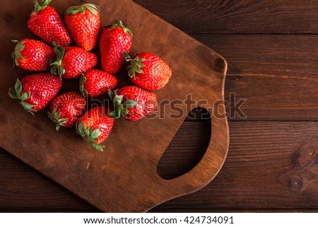 Fresh strawberry on cutting board. Rustic ripe strawberry. Flat lay, top view - stock photo