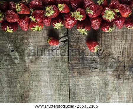 Fresh strawberry on weathering wooden background. Grunge style.