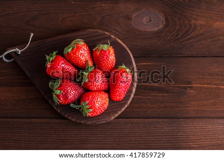 Fresh strawberry on wooden background. Rustic ripe strawberry top view, flat lay - stock photo