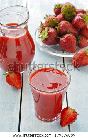 Fresh strawberry smoothie in drinking glass. Decoration: a  carafe of strawberry smoothies, fresh strawberry berries.  - stock photo