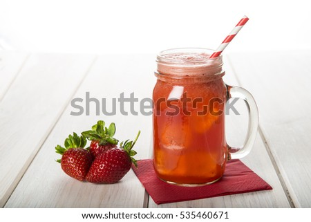 Fresh strawberry smoothie jar on a wooden table with a white background