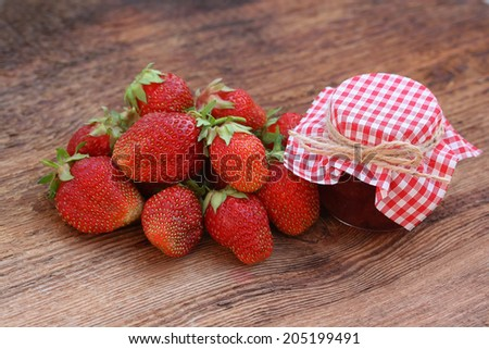 Fresh strawberry with a can of strawberry jam on an old wooden background - stock photo