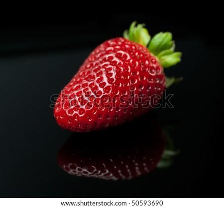 Fresh strawberry with leaf isolated on black background (macro) - stock photo