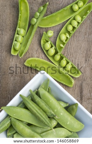 Fresh sugar snap peas in pod on rustic wooden background - stock photo