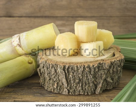 Fresh sugarcane cut into pieces on a wooden table.