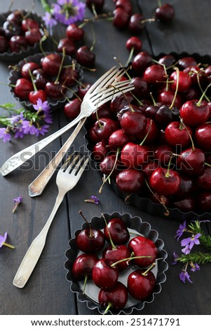 Fresh summer cherries and flowers in aluminum plates - stock photo