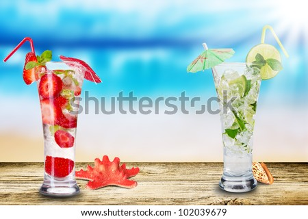 Fresh summer cocktails on wooden table. Blur beach on background - stock photo