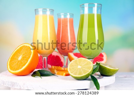 Fresh summer cocktails on wooden table on bright blurred background - stock photo