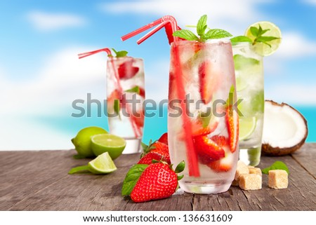 Fresh summer drinks on wooden table with blur sea background - stock photo