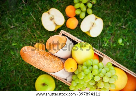 Fresh Summer Food Fruit Basket Picnic Basket Apples Grapes Bread Orange Green Grass - stock photo