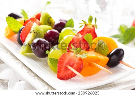 Fresh summer fruits on sticks. With mint leaves. Tilt-Shift. Focus is on first stick of fruits.  - stock photo