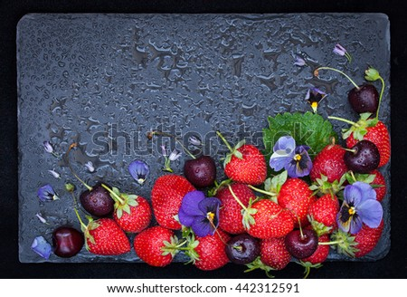 Fresh summer ripe strawberry and cherry on dark background, decorated with flowers and ice, top view, copy space - stock photo