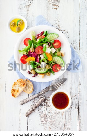 Fresh summer salad with cherry tomatoes, spinach, arugula, romaine and lettuces in a plate on white wooden background, top view - stock photo