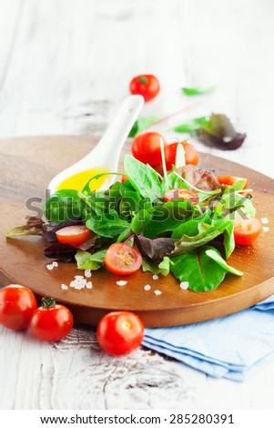 Fresh summer salad with cherry tomatoes, spinach, romaine and lettuce on a wooden chopping board on rustic white background, selective focus - stock photo