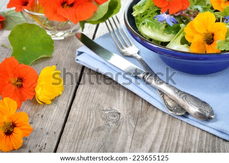 Fresh summer salad with edible flowers nasturtium, borage flowers in a bowl. Copyspace. - stock photo