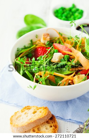 Fresh summer salad with green beans, spinach leaves and strawberries on white wooden background, selective focus - stock photo