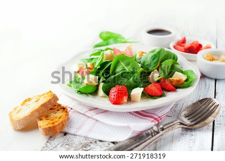 Fresh summer salad with strawberries, spinach leaves and feta cheese on white wooden background, selective focus - stock photo