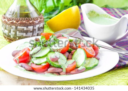 Fresh summer salad with tomatoes, cucumbers and beans under the green herb sauce - stock photo