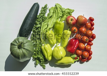 Fresh summer vegetables harvest from garden. Top view on multiple kinds of vegetables lying on white wooden table.  - stock photo