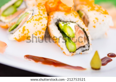 Fresh sushi rolls with asparagus and caviar on a plate decorated with soy sauce and wasabi selective focus - stock photo