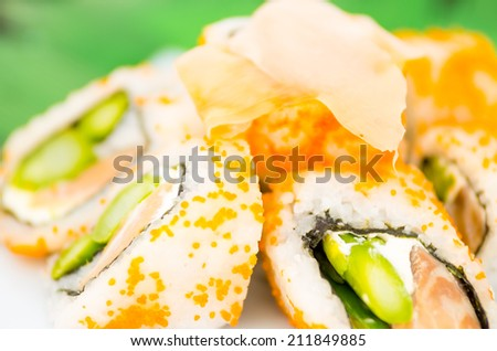 Fresh sushi rolls with asparagus and caviar on a plate with ginger on top selective focus - stock photo