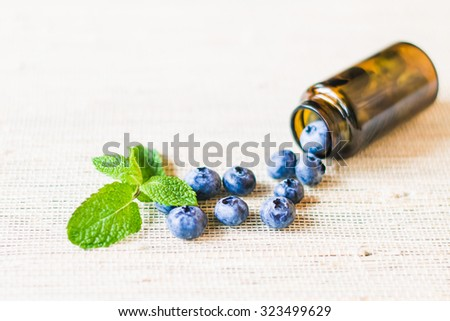 Fresh sweet blueberry fruit and leaf of mint in medical bottle from pills. Dessert healthy food. Group of ripe blue juicy organic berries. Raw summer diet. Delicious nature vegetarian ingredient - stock photo