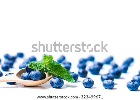 Fresh sweet blueberry fruit and leaf of mint in wooden spoon. Dessert healthy food. Group of ripe blue juisy organic berries. Raw summer diet. Delicious nature vegetarian ingredient - stock photo