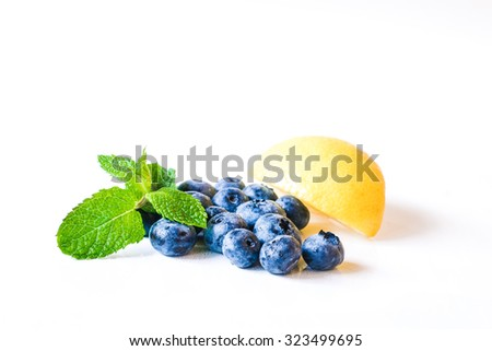 Fresh sweet blueberry fruit and leaf of mint with lemon. Dessert healthy food. Group of ripe blue juicy organic berries. Raw summer diet. Delicious nature vegetarian ingredient. Juicy blueberry - stock photo