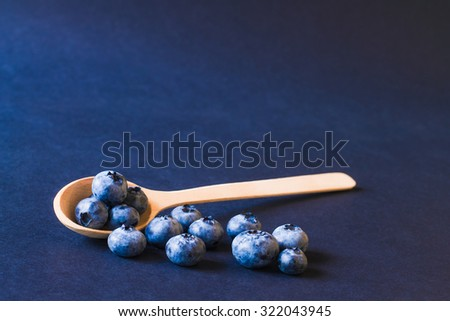 Fresh sweet blueberry fruit in the wooden spoon. Dessert healthy food. Group of ripe blue jui?y organic berries. Raw summer diet. Delicious nature vegetarian ingredient. Black background. - stock photo