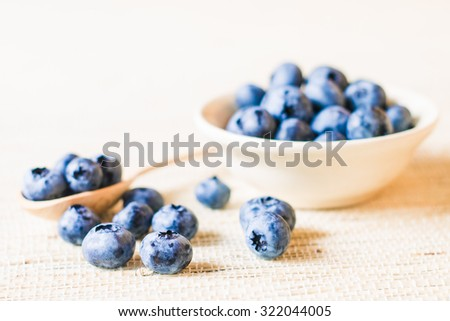 Fresh sweet blueberry fruit in wooden spoon. Dessert healthy food. Group of ripe blue jui?y organic berries. Raw summer diet. Delicious nature vegetarian ingredient. Wooden background. - stock photo
