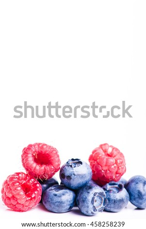 Fresh sweet blueberry, raspberry fruit. Dessert healthy food. Group of ripe blue juisy organic berries. Raw summer diet. Delicious nature vegetarian ingredient. White background. - stock photo