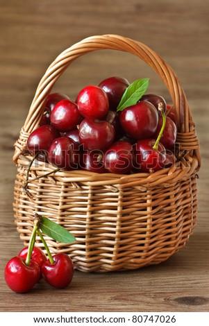Fresh sweet cherries in a wicker basket. - stock photo
