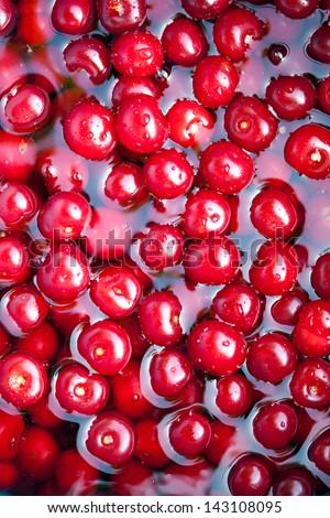 Fresh sweet cherries in water. Macro image. - stock photo