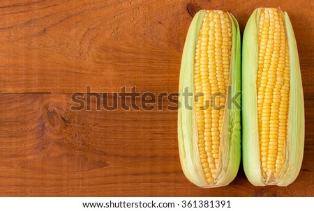 Fresh sweet corn on wooden table.  - stock photo