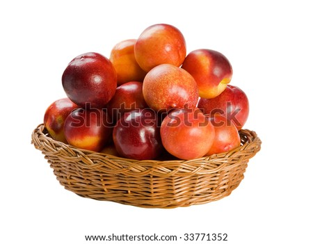 Fresh sweet nectarines in basket on white background